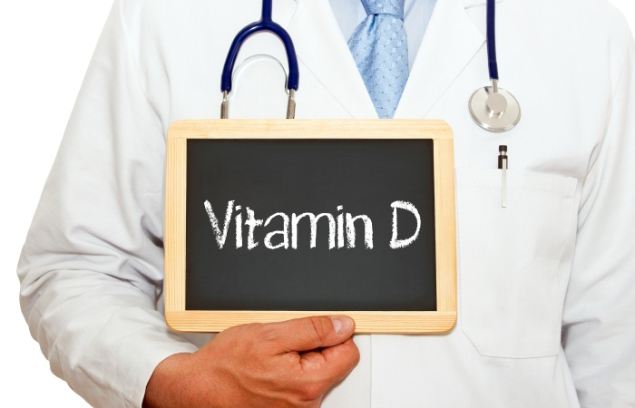 Vitamin D - Doctor with chalkboard on white background